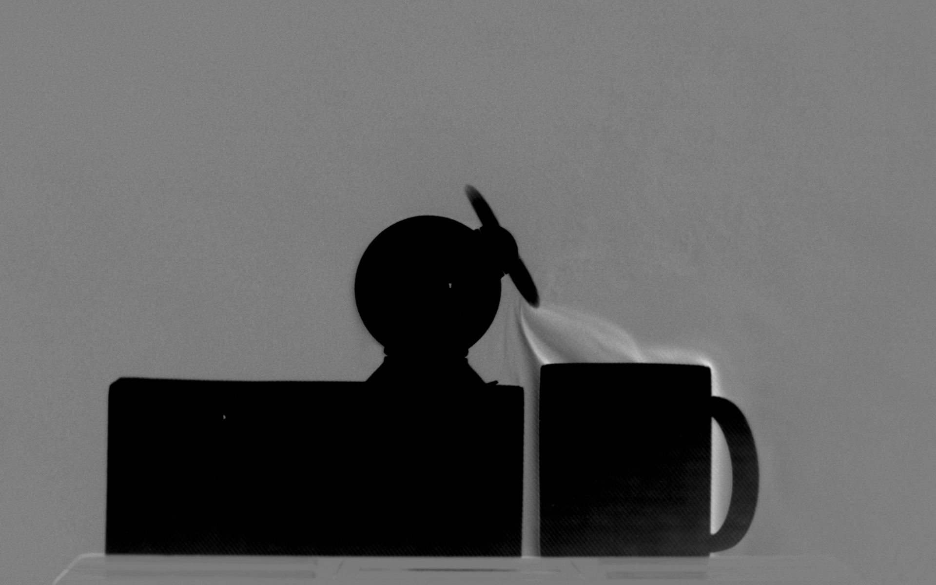 Schlieren image of a fan drawing a thermal updraft off of a teacup